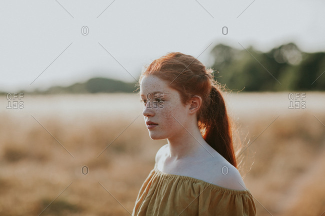 Young teen redhead girl in a field at sunset