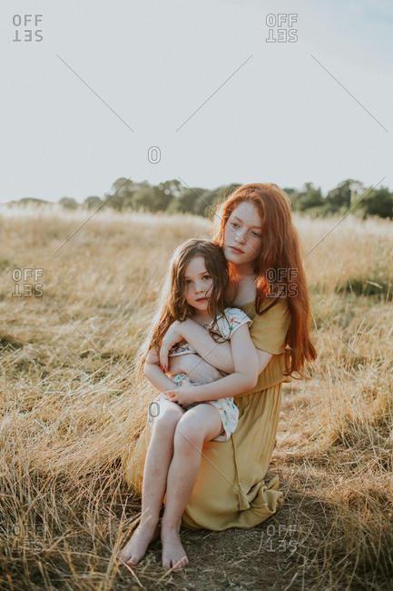 Teen girl holding her little sister in her lap at sunset