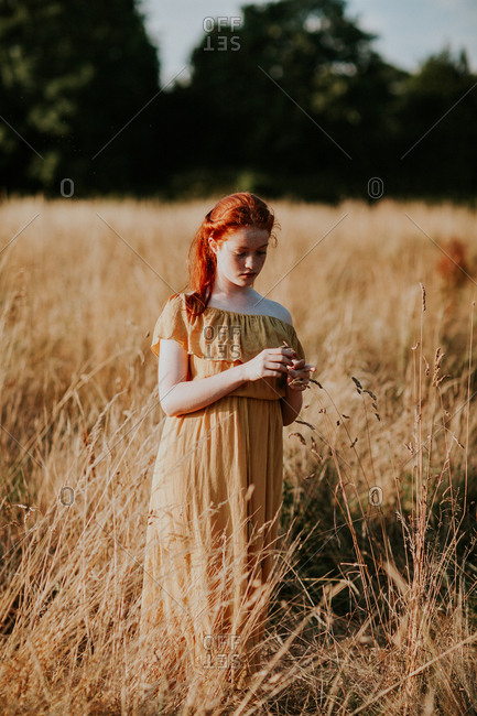 Beautiful red haired teen redhead girl in a field at sunset
