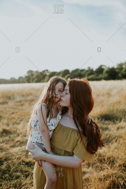 Girl giving her little sister a kiss on the cheek at sunset in a field