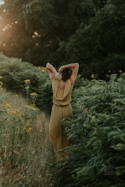 Woman walking in a yellow dress through nature at sunset