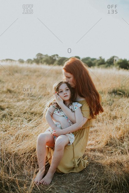 Girl holding and kissing her little sister a kiss on the cheek at sunset in a field