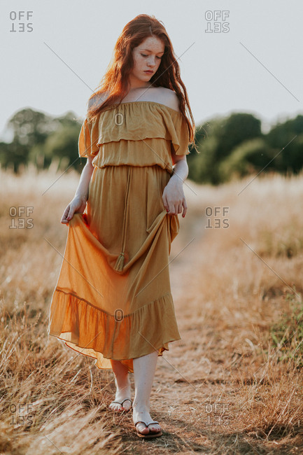 Adolescent redhead girl walking in a field at sunset