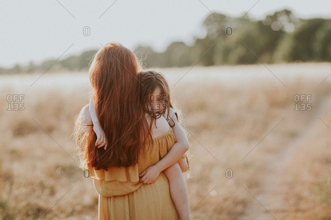Girl carrying her little sister at sunset in a field