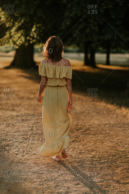 Rear view of woman walking in a yellow dress at sunset