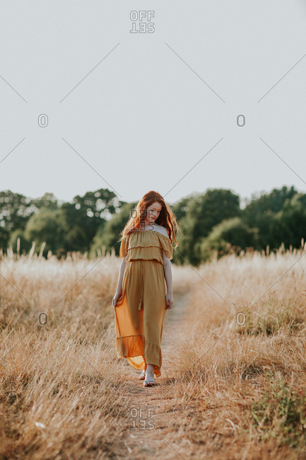 Young redhead girl walking in a field at sunset