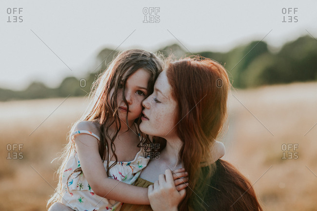 Girl holding her little sister outdoors at sunset