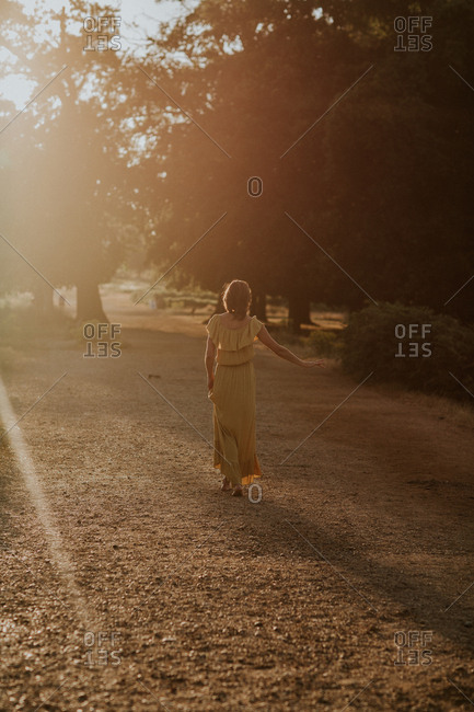 Rear view of woman walking in a yellow dress at sunset with lens flare
