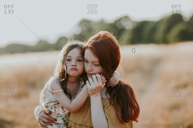 Girl carrying her little sister outdoors at sunset