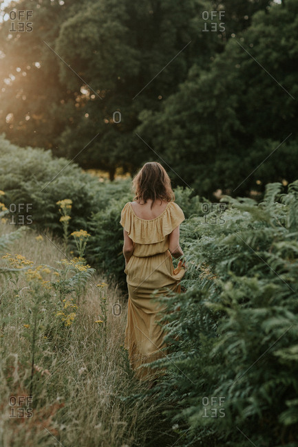 Woman wearing a yellow dress in nature at sunset