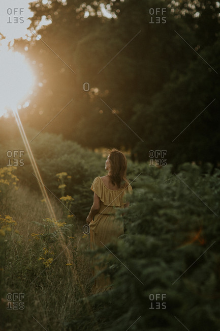 Woman wearing a yellow dress looking up at the sunset