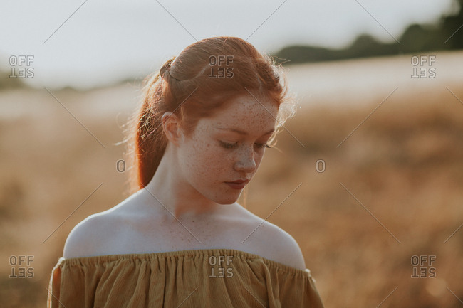 Young redhead girl with freckles in a field at sunset