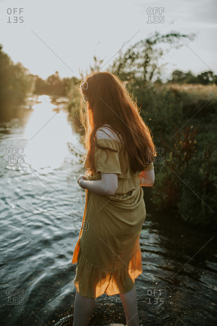 Adolescent redhead girl walking in a creek at sunset