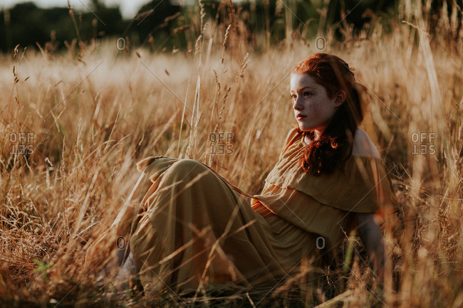 Young redhead teen resting in a field at sunset
