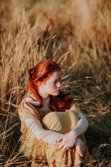 Young redhead teen sitting in a field at sunset