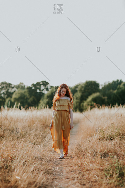 Beautiful teen with long red hair walking in a field at sunset