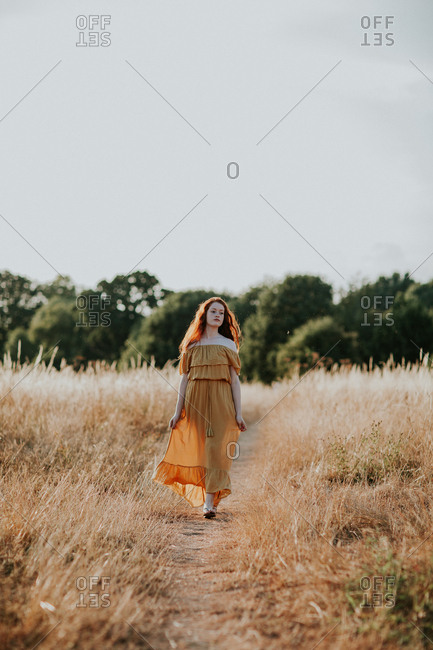 Beautiful teen with red hair walking in a field at sunset