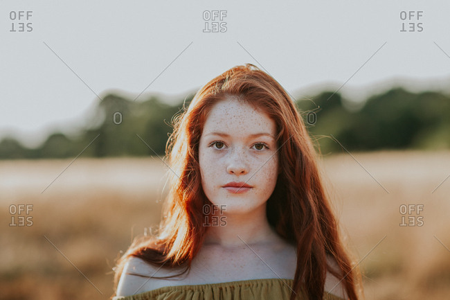 Portrait of a beautiful teen with red hair in a field at sunset