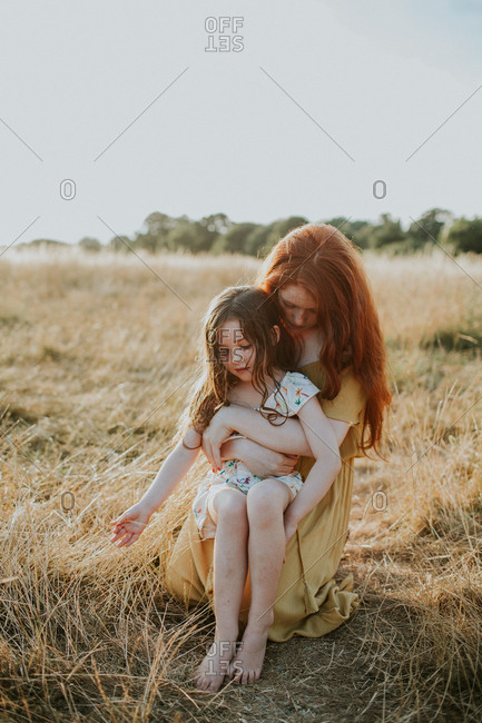 Sisters sitting together in a field at sunset