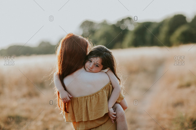 Girl carrying her little sister through a field at sunset