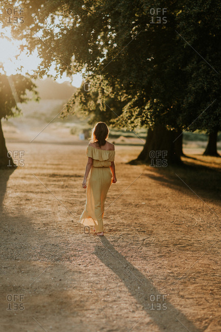 Rear view of woman walking in a yellow dress at sundown