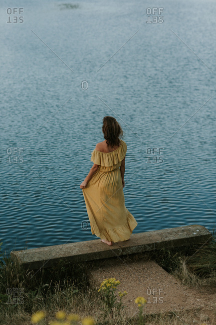 Rear view of woman in a yellow dress standing on the edge of a lake