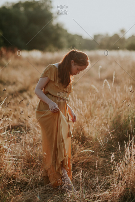 Beautiful teen with ginger hair walking in a field at sunset