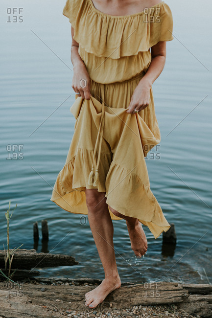 Woman in a yellow dress stepping out of a lake