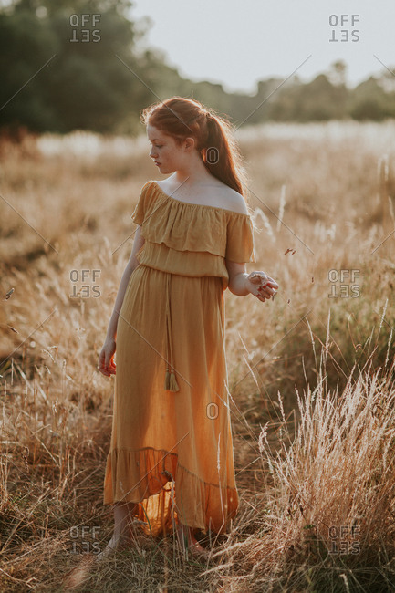 Beautiful young girl with ginger hair walking in a field at sunset