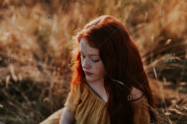 Portrait of a beautiful teen with ginger hair in a field at sunset