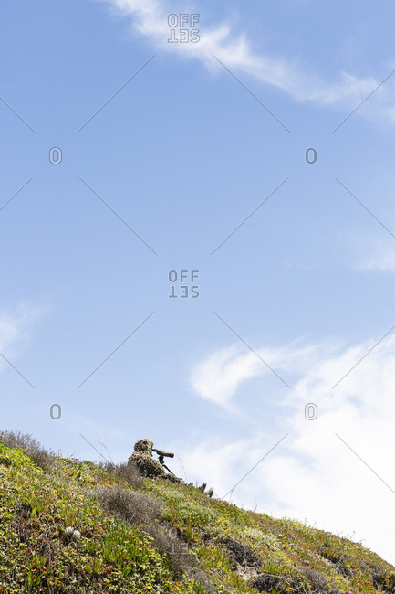 Nature photographer in camouflage sitting on top of hill