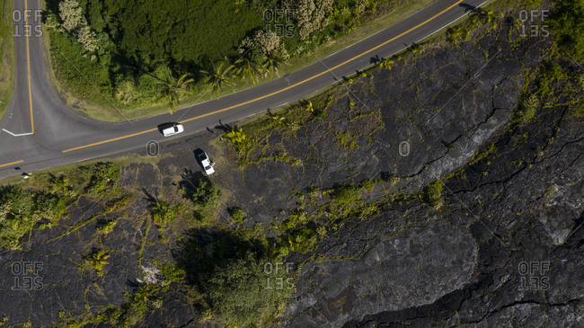 Aerial view of highway and vehicles on a volcanic terrain