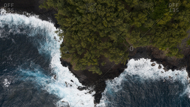 Aerial view over blue waves rolling into seashore with trees