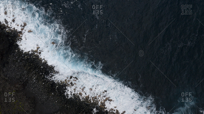 Aerial view over rough blue waves rolling into rocky seashore