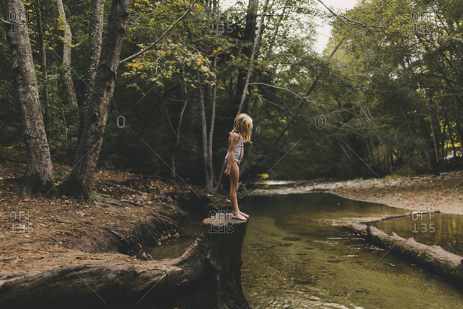 Little girl preparing to jump into a river