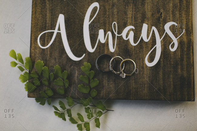 "Wedding rings on a board that reads ""Always"""