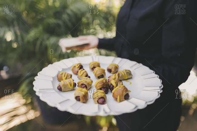 Woman serving wedding sausage appetizers