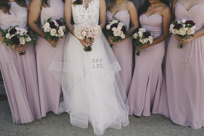 Bride and bridesmaids holding rose bouquets
