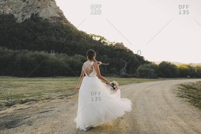 Bride walking on dirt road from behind