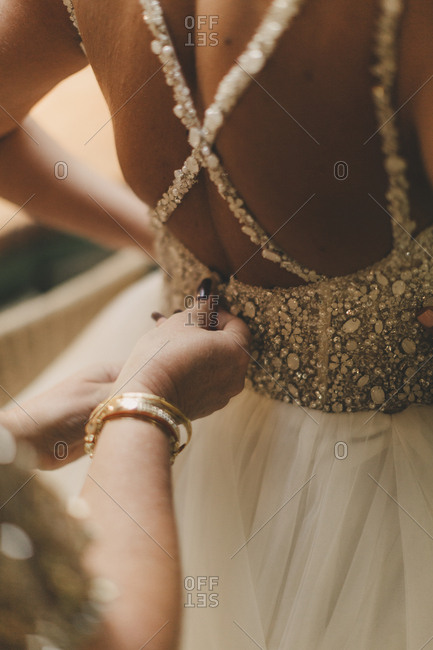 Woman zipping bride's dress