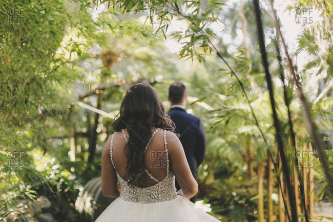 Bride walking on through tropical forest to her groom