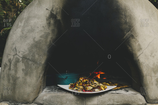 Large pile of grilled vegetables on an outdoor stone oven
