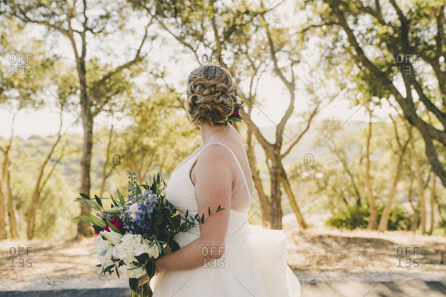 Blonde bride holding bouquet and looking away