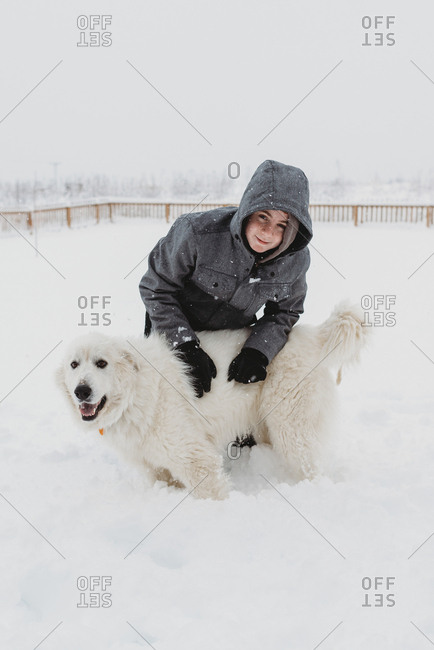 Boy with large white dog in the snow