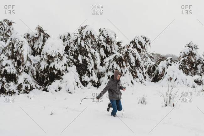 Young adolescent boy outside in winter holding a stick