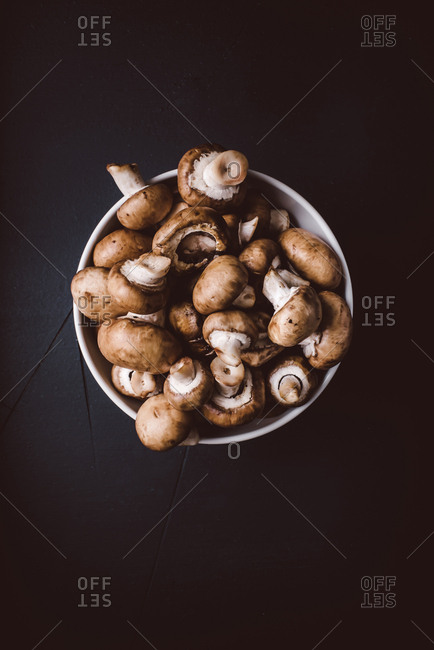 Bowl full of mushrooms on a dark background