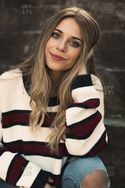 Portrait of a pretty blonde girl smiling with a striped sweater