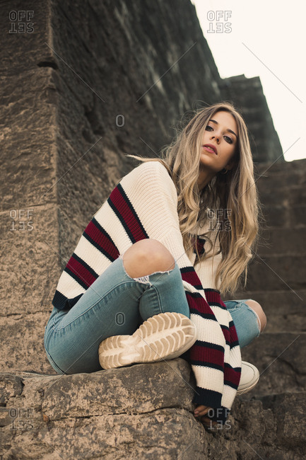 Portrait of a pretty blonde girl sitting with a striped sweater