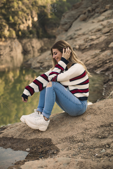 Portrait of a pretty blonde girl sitting smiling with a lake in the background