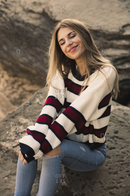 Portrait of a pretty blonde girl sitting on a rock breathing calm